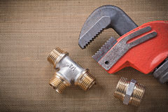 Plumbers wrench brass plumbing fixtures on mesh filter grid Stock Image