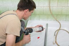 Plumbing. Plumber using silicone cartridge for fixing aluminum batten of shower cabin royalty free stock photo