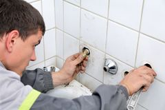 Plumbing. Plumber fixing pipeline with tool in handsand checking leaking stock photos