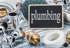 Plumbing and blackboard on wooden table Royalty Free Stock Photo