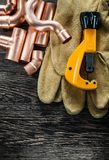 Plumbing brassware pipe cutter leather protective gloves on wood. En board Royalty Free Stock Photography