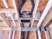 Plumbing Connections in a Ceiling. PVC and copper piping and hoses run through the walls of a home for the home water connections Stock Image