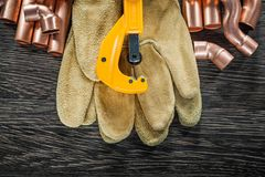 Plumbing copper water pipe scissors leather safety gloves on woo. Den board Stock Images
