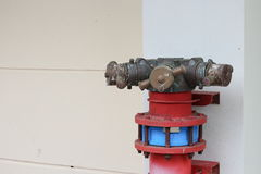 Plumbing fire hydrant in a metal line wall. Fireplug with valves royalty free stock photo