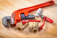 Plumbing fixtures and monkey wrench on wooden board Royalty Free Stock Image