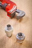 Plumbing fixtures and monkey wrench on wooden board Stock Images