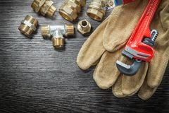 Plumbing monkey wrench pipe fittings protective gloves water val. Ve on wooden board Stock Photography