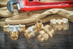 Plumbing monkey wrench pipe fittings protective gloves on wooden. Board Royalty Free Stock Photography