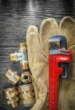 Plumbing monkey wrench pipe fittings safety gloves on wooden boa. Rd Royalty Free Stock Image