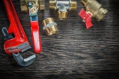 Plumbing monkey wrench pipe fittings water valve on vintage wood. En board Royalty Free Stock Image