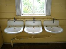 Plumbing: old wash basins. Row of old wash basins in old schoolhouse Royalty Free Stock Photos