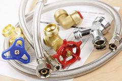 Plumbing parts. Plumbing valves hoses and assorted parts with estimate sheet Stock Photography