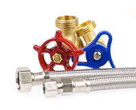 Plumbing parts. Blue and red plumbing valves with metal hoses Stock Image