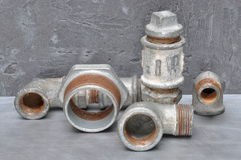 Plumbing parts on grey metal board Stock Photos