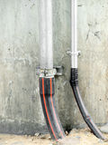 Plumbing pipe against stucco wall Stock Images