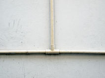 Plumbing pipe against stucco wall Royalty Free Stock Image