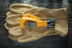 Plumbing pipe cutter leather protective gloves on wooden board.  Stock Photography