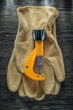 Plumbing pipe cutter leather safety gloves on wooden board.  Stock Photo