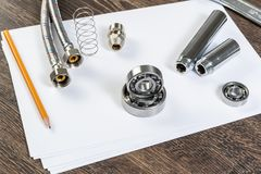 Plumbing pipeline and ball bearings. Laying on table. Water fittings and connections with segments of braided hose. Steel details for engine mechanisms. House royalty free stock photo