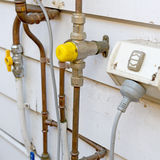 Plumbing Pipes. Various copper plumbing pipes and outdoor power outlet stock photo