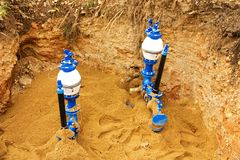Plumbing and pipes. Water pipes in the ground, sand around the new pipe, new plumbing pipes in the ground Royalty Free Stock Image