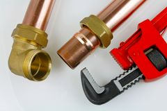 Plumbing pipework. A plan view of an adjustable wrench and 15mm copper pipework with a compression fitting on a grey background stock photo