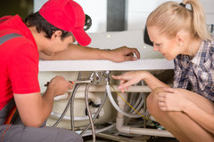 Plumbing. Professional plumber. Plumbing repair service. Woman is showing damage plumbing Royalty Free Stock Images