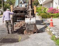 Plumbing Repair Man and excavator. Scoop digging, Repair of pipe water and sewerage on road, worker fixing broken water main Royalty Free Stock Photo