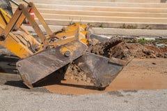 Plumbing Repair Man and excavator scoop digging, Repair of pipe. Water and sewerage on road, worker fixing broken water main Royalty Free Stock Image