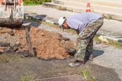 Plumbing Repair Man and excavator scoop. Digging, Worker using a small tracked excavator to dig a hole to fix a water on road, and soft-focus background Royalty Free Stock Photo