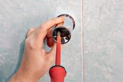 Plumbing repair, replace vertical holder shower bracket, using s Royalty Free Stock Image