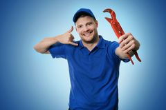 Plumbing services - plumber with wrench showing phone call gesture. On blue background Stock Photo