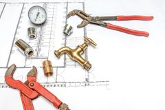 Plan plumber and wrench. Plumbing Tools Arranged On House Plans whit wrench and water valves Royalty Free Stock Images
