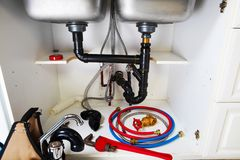 Plumbing tools on the kitchen. Renovation background royalty free stock images