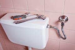 Plumbing tools lying on toilet Royalty Free Stock Photography