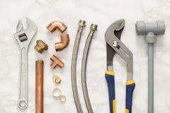 Plumbing Tools and Materials on Marble Background. A selection of plumbing tools and materials including a spanner, vice grip, and copper pipe on a marble stock photo