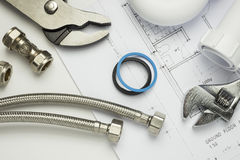 Plumbing tools and parts on house plans Stock Image