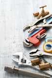 Plumbing tools. Various type of plumbing tools on white textured background Royalty Free Stock Images
