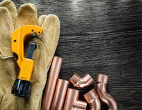 Plumbing water pipe scissors leather protective gloves on wooden. Board Royalty Free Stock Image