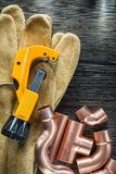 Plumbing water pipe scissors leather safety gloves on wooden boa. Rd Royalty Free Stock Image