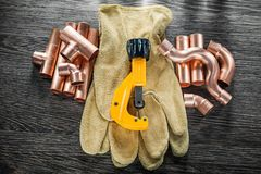 Plumbing water pipe scissors leather safety gloves on wooden boa. Rd top view Royalty Free Stock Images