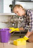 Plumbing. Woman while cleaning the floor in the bathroom royalty free stock image