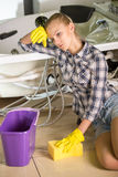 Plumbing. Woman is cleaning the floor. A bucket of water Royalty Free Stock Image