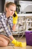 Plumbing. Woman mopping up. She is calling to plumbing Stock Photos