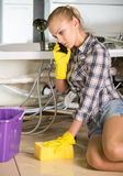 Plumbing. Woman mopping up. She is calling to plumbing Royalty Free Stock Photo