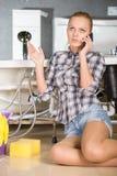 Plumbing. Woman mopping up. She is calling to plumbing Stock Image
