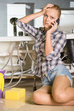 Plumbing. Woman mopping up. She is calling to plumbing Royalty Free Stock Images