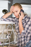 Plumbing. Woman is talking on the phone with customer service Royalty Free Stock Image