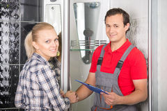 Plumbing. Young women and plumber are looking at the camera while standing in the bathroom Royalty Free Stock Photos