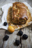 Plumcake with blackberries and plums. On a table Stock Images